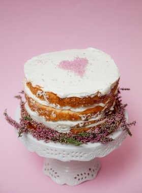 Tender shabby homemade cake with a pink heart on a top and heather flowers on the bottom. Pink background