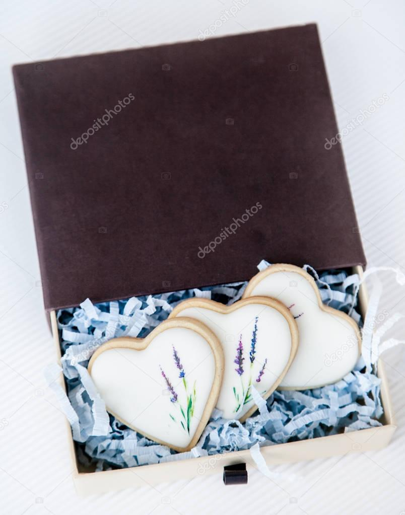 Hand painted cookies topped with white glaze in a gift box. Hand drawn with edible coloring lavender flower stems motive. Natural light