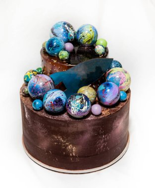 Modern trendy 2-tier layered cake with chocolate hand painted planets and rocket on a white background.