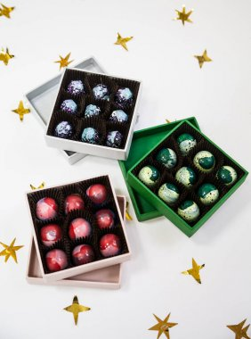 Chocolate handpainted luxury candy bonbons in a gift box. White background with golden stars.