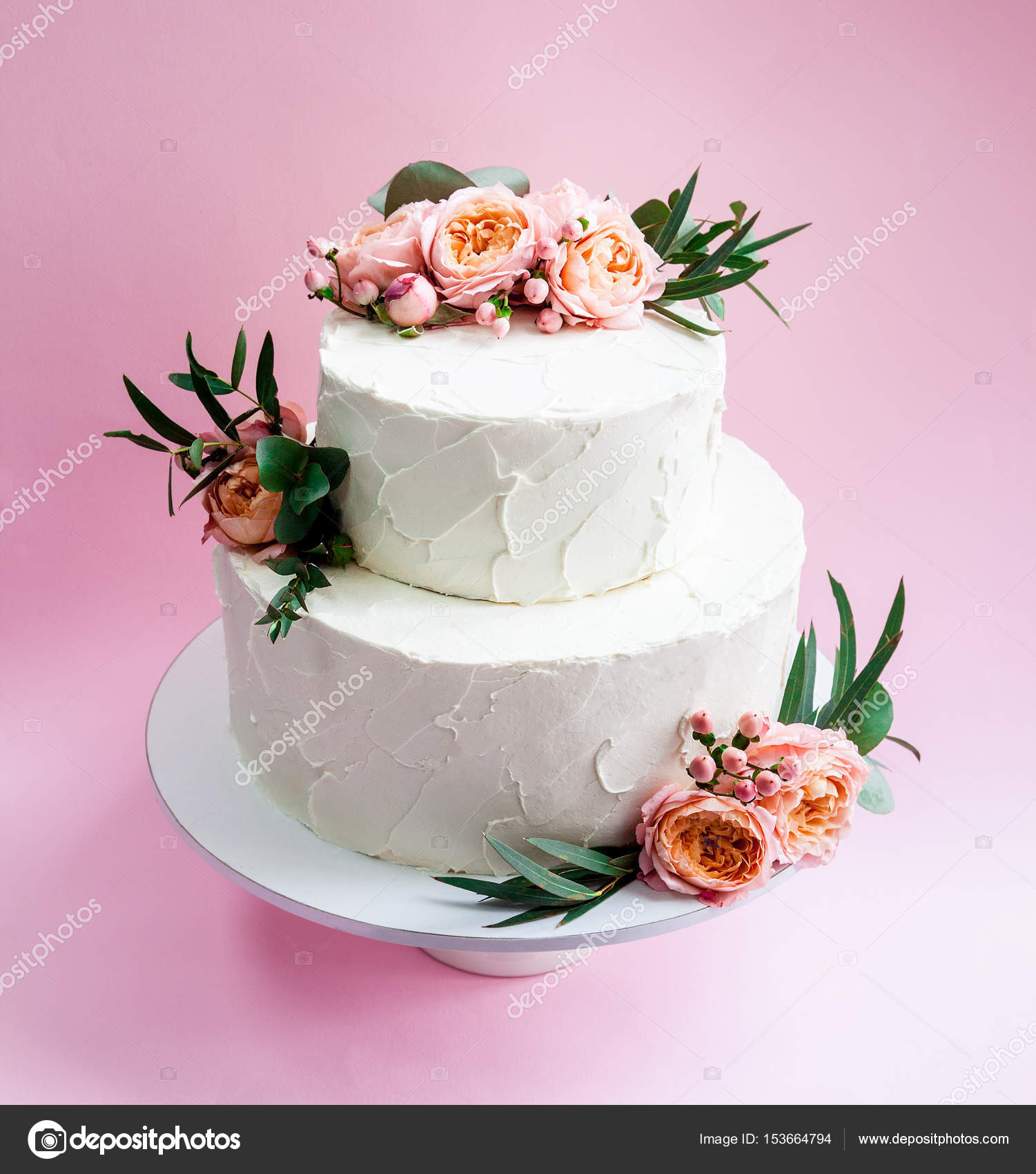 Elegant wedding tiered cake decorated with fresh roses and freesia ...