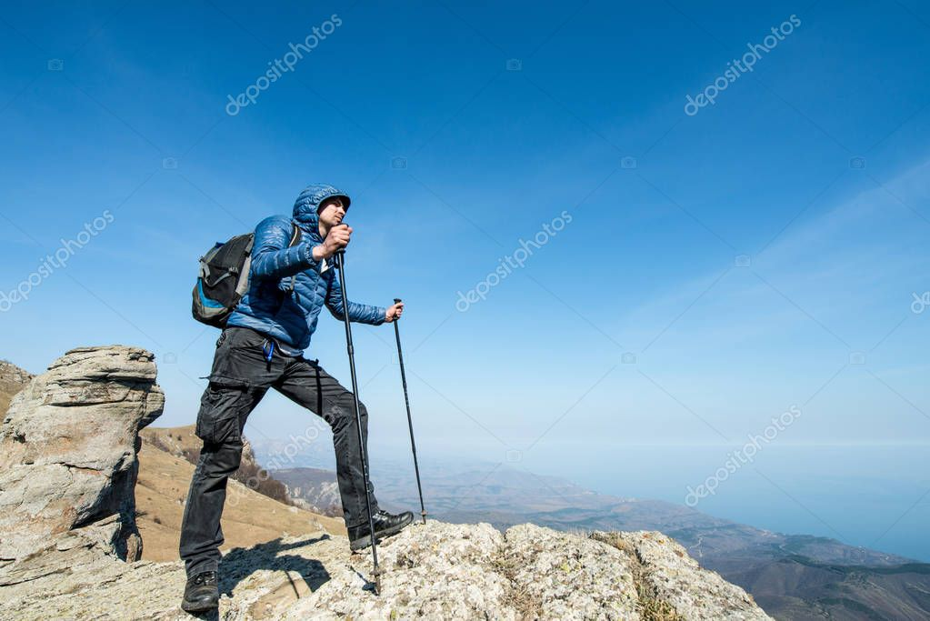 Traveler with trekking sticks and a backpack on the top of the m