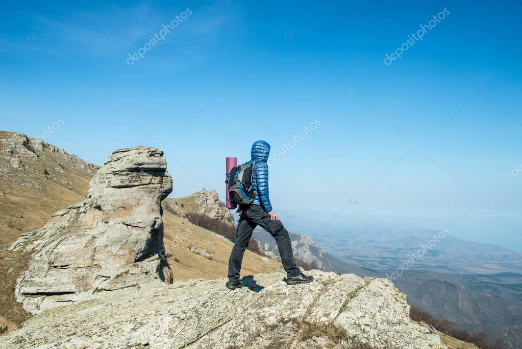 Traveler with backpack on the top of the mountain