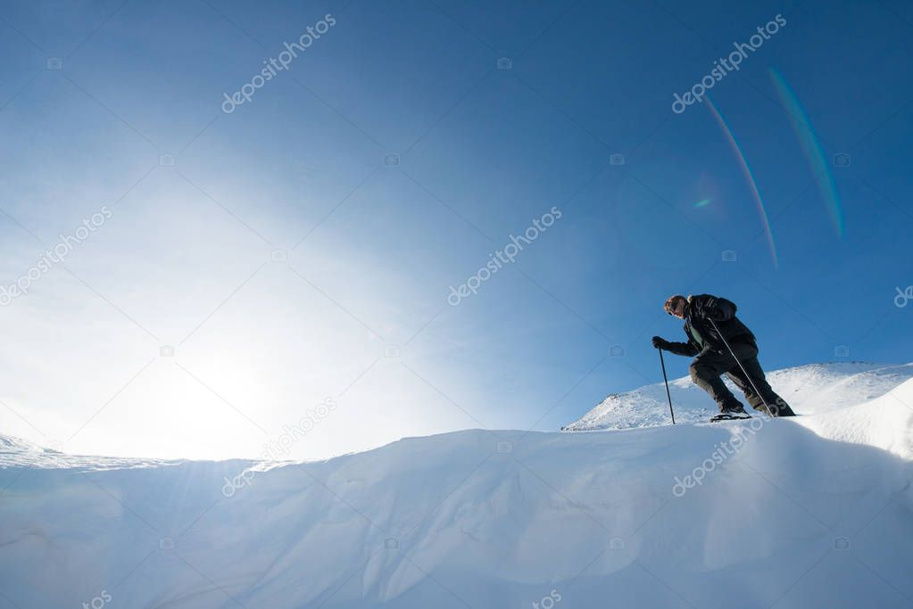 climber with trekking poles in the snowy mountains