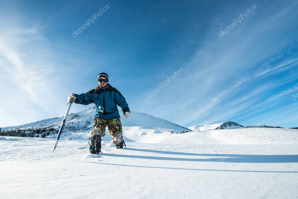 climber with an ice ax walks in the snowy mountains