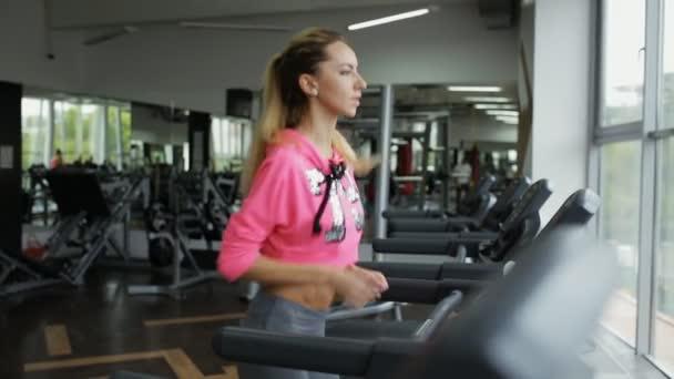 Dospělé sportovní žena běží na běžeckém pásu v tělocvičně