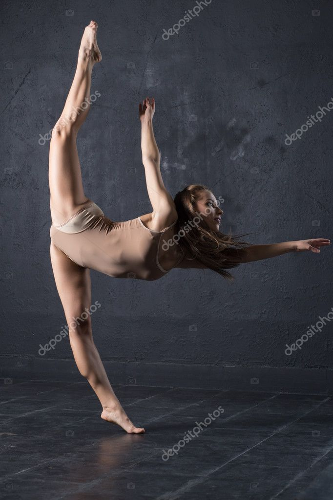 Pretty girl dancing on gray textured wall background