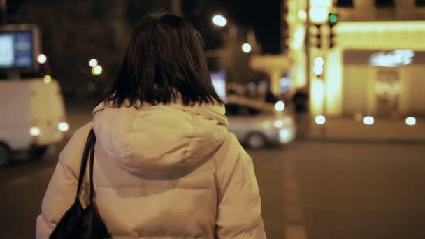 Frau steht vor einer Ampel und wartet darauf, die Straße zu überqueren