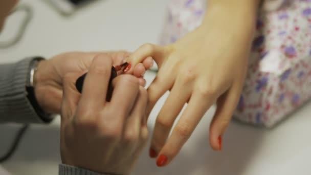 Kosmetička se vztahuje přesně na nehty klienta s červenými nehty