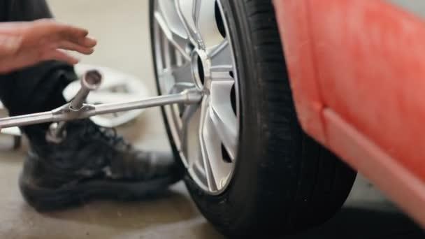 Autó szerelő tartószerkezethez autó kerék felemelt autó mellett csavarkulcs