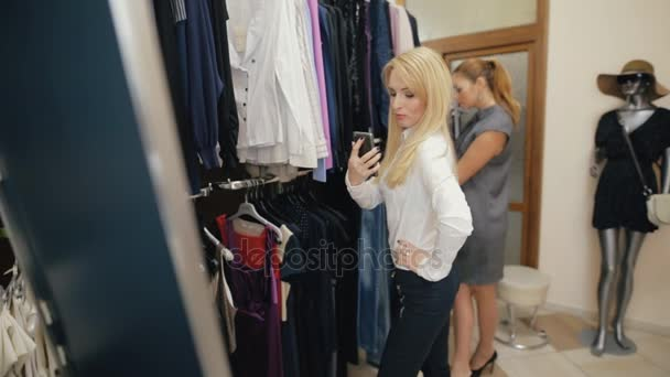 Přátelé vyzkoušejte na oblečení v obchodě, jedna žena selfie v nové tričko