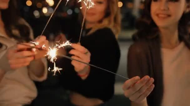 Drei junge Mädchen feiern mit einem Funkeln drinnen