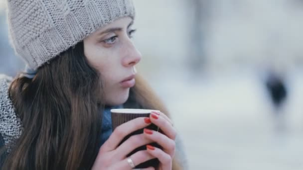 Young woman drinking hot tea in winter evening