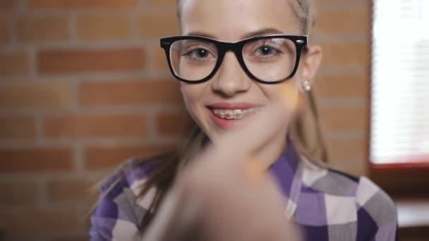 Teenie-Mädchenporträt. Schüler mit Brille und Zahnspange.
