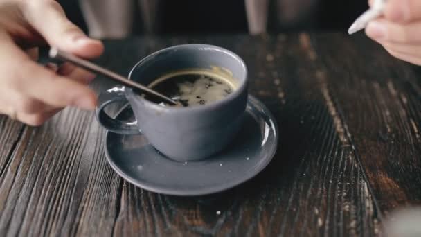 Closeup sypat cukru v šálku kávy