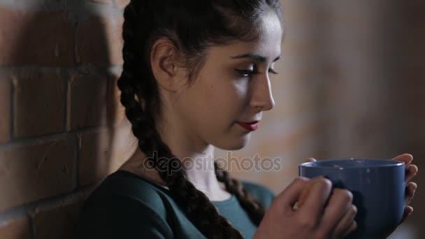 Woman drinking tea at brick wall background in dark room