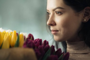 Closeup portrait of pretty women holding bouquet of tulips