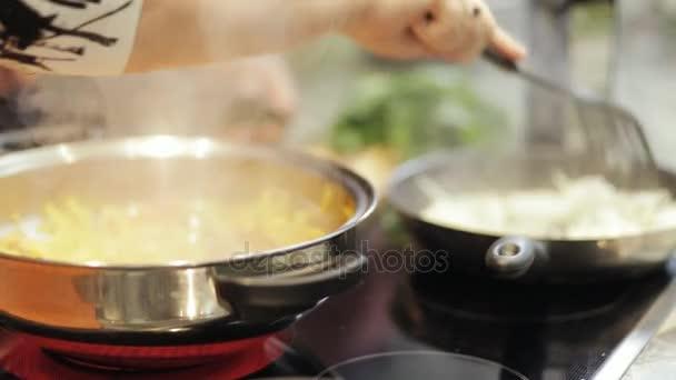Detail ze dvou rukou kuchař vaření v kuchyni restaurace