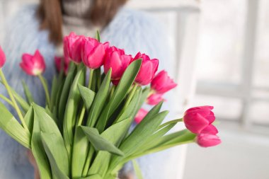 Cropped shot of unrecognizable girl holding bouquet of pink tulips