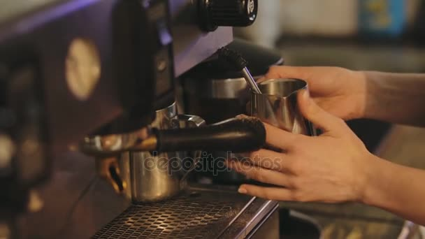 Close up of barista hands steaming milk for a latte or cappuccino