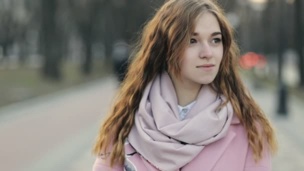 Close up portrait - beautiful young woman looks around in street