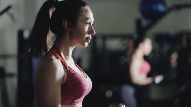 Sportovní žena zvedání JEDNORUČKY v tělocvičně, biceps cvičení na zrcadlo