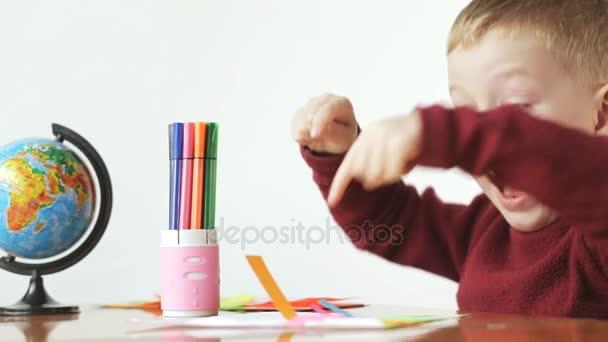 Malý chlapec lepidla barevný papír na bílém pozadí. Předškolní vzdělávání