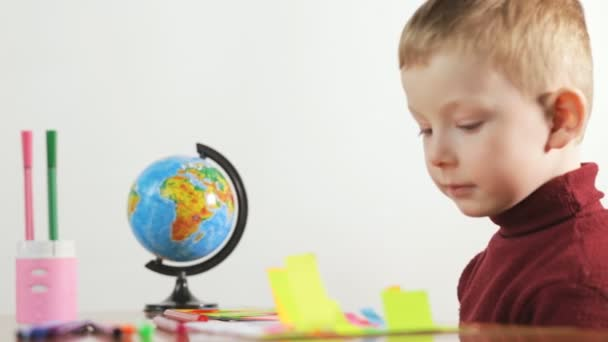 Little boy draws a markers on color paper, white background.