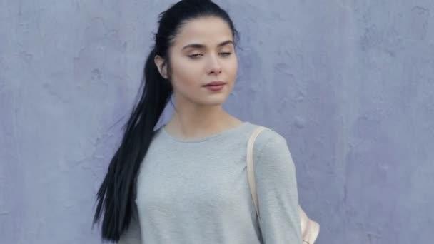 Módní elegantní žena pózuje na fialové zdi s taškou