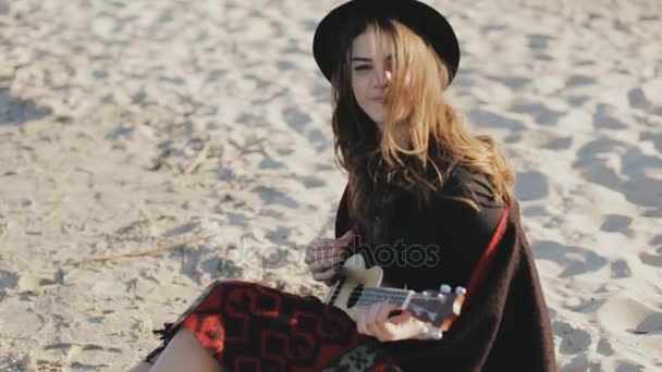 Happy young woman playing on ukulele at beach