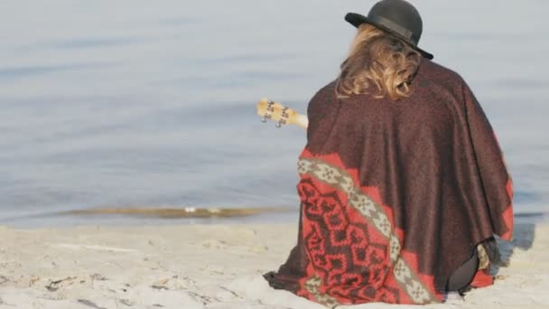 Happy young woman playing on ukulele at beach - back view