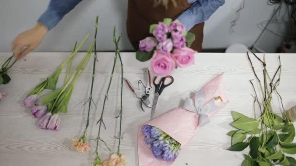 Florist woman make a flowers bouquet - top view