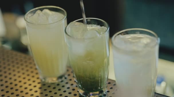 Barmen mixing cocktail in glasses