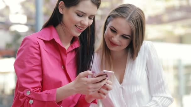 Two stylish women friends looking to smartphone in city