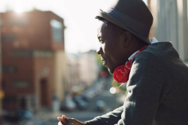African american man with headphones looking at city