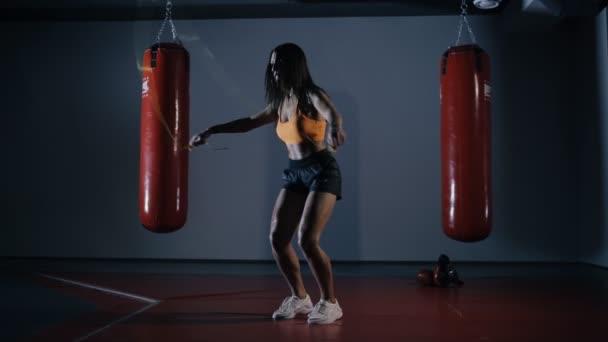 Mladá žena boxer skákání na švihadla v temné chodbě