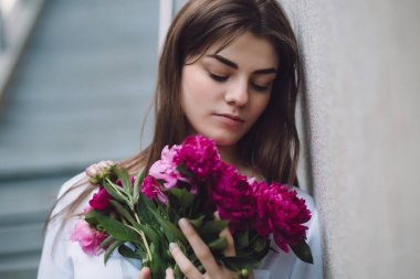 Woman holding flowers peonies bouquet