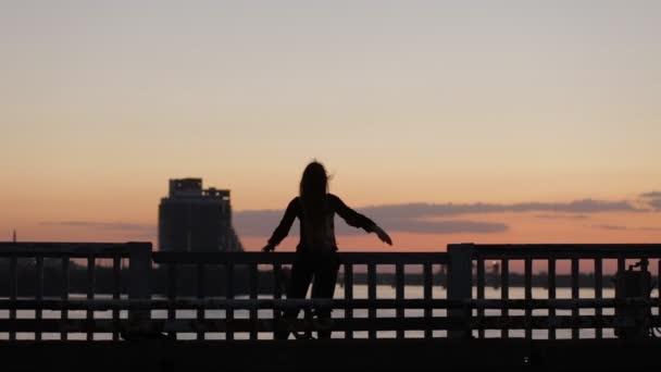 Silueta ženy užívat svobody na mostě v večer