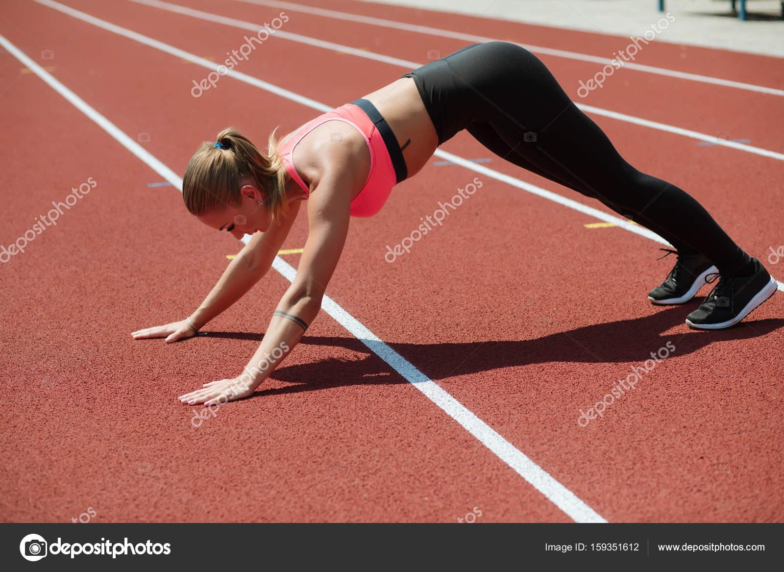 9b8f0b46213 Νεαρή γυναίκα σπορ αθλητής σε αθλητικά είδη διαδρομών στο στίβο του  σταδίου, υπαίθρια προπόνηση —