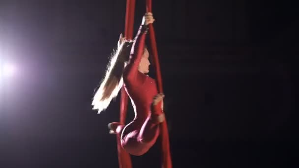 Equilibrium gymnast balancing and rotating on a red silk