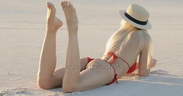 Szexi nő feküdt egy fürdőruhát, pihenő- és pihentető tengerparti homok