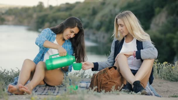 Best friends hiking together. Two young women drinking hot tea outdoors. Girls travel with adventure.