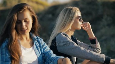 Two young traveler women. Fashion style of girls sitting and wearing sunglasses at sunset.