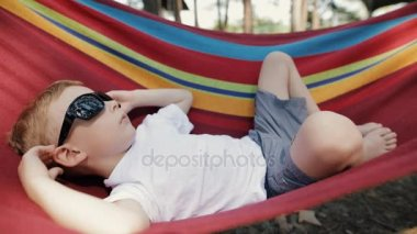 Cheerful little boy with sunglasses lying on hammock in a pine forest, he resting at nature and looking to sky