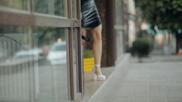 Fashion model walking on a city street in evening, slow motion