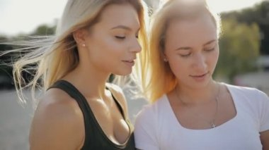 Girls friends looking to smartphone in a beach at summer holidays, slow motion