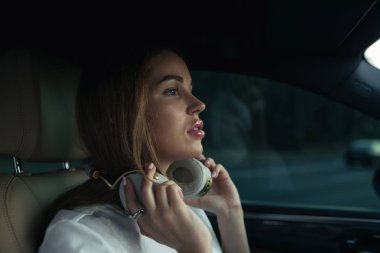 Luxury woman listen music with headphones in her comfortable car