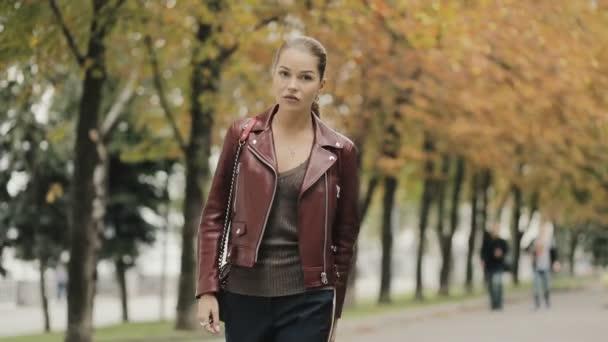 new product bffc1 73069 L'autunno sta arrivando. Donna elegante in giacca di pelle Bordeaux a piedi  in città strada, slowmotion.