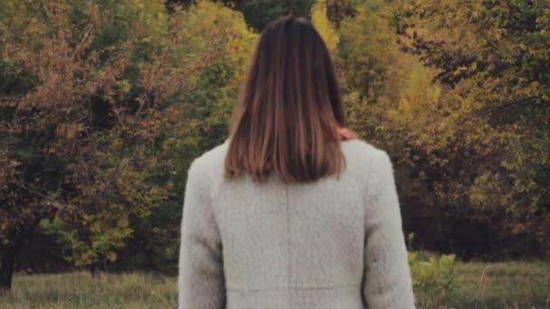 Pohled zezadu na ženy při pohledu na žluté barevné listí v lese stromy na podzim zatažený den