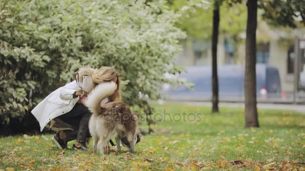 Woman playing with a dog husky in park at the autumn day, slow motion